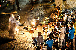 People dancing to and listening to Gnawa music during evening in Jemaa el Fna square, Merrakesh, Morocco