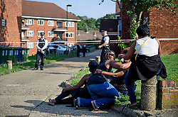 © Licensed to London News Pictures. 15/09/2016. London, UK. Grieving relatives at scene of a double shooting in a block of flats in East Finchley. Police were called by London Ambulance Service at 06:25hrs this morning to reports of two people injured at an address in north London. A man and a woman were found with gunshot injuries. Both were pronounced dead at the scene. Photo credit: Ben Cawthra/LNP
