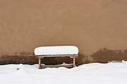 Snow-covered bench near adobe wall
