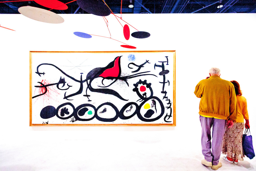 """Painting by Joan Miró entitled """"La March Penible Guidee Par L'Osieau Flamboyant Du Desert"""" at Art Basel Miami Beach 2010. The mobile scupture hanging from above is by Alexander Calder."""