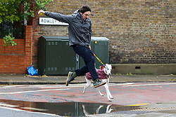 © Licensed to London News Pictures. 08/05/2021. London, UK. A man and his dog jump over a puddle following heavy rainfall overnight in north London. More rain is forecasted for the South East of England today. Photo credit: Dinendra Haria/LNP