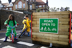 © Licensed to London News Pictures. 15/11/2020. London, UK. AMIRA AURORA, 3yrs old (L) and IDRIS 5 yrs old (R) with their bikes next to the new sign at the entrance of Etherley Road in Haringey as it becomes the first street in Haringey, north London to close to motorcycles and cars, and only open for pedestrians and cyclist to increase road safety. <br /> <br /> *** Permission Granted***<br /> <br /> Photo credit: Dinendra Haria/LNP