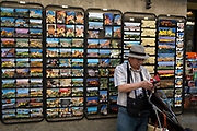 A tourist uses phone apps alongside a rack of postcards showing local scenes and historical ocations, on 27th May, 2017, in Carcasonne, Languedoc-Rousillon, south of France. Situated on the right bank of the Aude, the City, a medieval village that is still inhabited, has 52 towers and two concentric walls totalling 3 km in length.