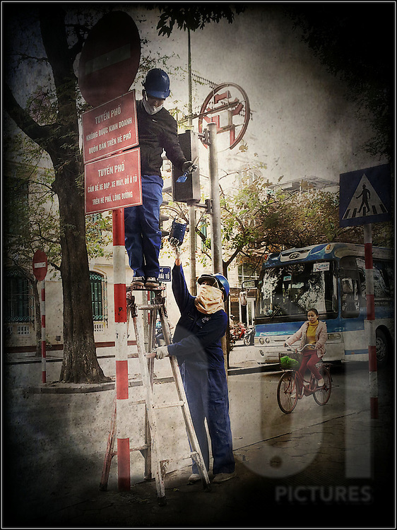 Worker stands on a ladder to paint a street sign while another worker holds up the paint can, Hanoi, Vietnam, Southeast Asia