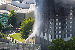 London, June 14th 2017. A fire rages through a residential tower block, Grenfell Tower, in Kensington, West London, with the entire building engulfed in flames. More than 200 firefighters are attending the incident and there are reports of people trapped inside. No figures are available as to casualties. PICTURED: Firefighters water jets appear to be able to reach only the lower floors of the 27 storey building.