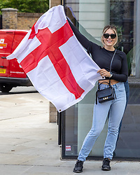 Licensed to London News Pictures. 08/07/2021. London, UK. An England fan poses with a flag next to an 'It's coming home' sign in Chelsea, southwest London as she celebrates England's win over Denmark last night at Wembley. Fans nursed hangovers this morning after celebrating into the night after England's dramatic win against Denmark in the Euro 2020 Semi-finals at iconic Wembley Stadium. The England team will be back at Wembley this Sunday (11 July 2021) for the first time since 1968 as they take on Italy for a chance to win the European cup for the first time ever. Photo credit: Alex Lentati/LNP