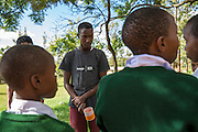 ICS volunteers demonstrate a method of filtering water through material at Endagikot school as part of the ICS Raleigh SWASH (school water, sanitation and hygiene plan) project. Mbulu, Manyara district, Tanzania. Working in partnership with the Diocese of Mbulu Development Department (DMDD); part of Caritas Tanzania.