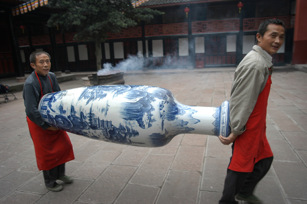 Workers carry a large blue and white vase in a Buddhist temple in Chengdu, incense burns in the background.