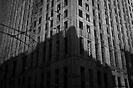 Exchange Building monochrome with electric bus wires and shadow of nearby building at 2nd and Marion in downtown Seattle, Washington state, USA