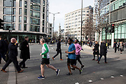 Lunchtime runners going for a healthy bit of exercise jogging around St Pauls in London, United Kingdom.