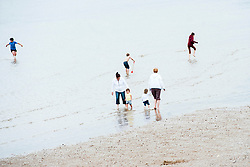 Women children and toddler paddle on Cleethorpes beach. Cleethorpes is situated on    Englands East Coast on the river Humber's tidal estuary. ..1 July 2012.Image © Paul David Drabble