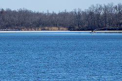 Fishermen in a small boat get an early start on the season by starting shortly after the Evergreen Lake begins to thaw in late February .  McLean County IL