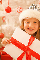 Close up of a smiling girl in a furry hat holding Christmas gift