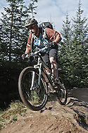 """Mountain biker (Tom Hutton)  descending fast flowing red section, """"The 8"""" red track, Gisburn Forest"""