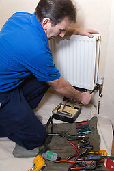 Gas man using pliers to unscrew a radiator valve,