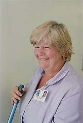 Portrait of female domestic assistant from Hotel Services smiling and holding mop,