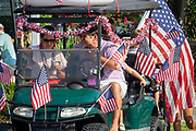 A golf cart float decorated with flags during the annual Independence Day golf cart and bicycle parade July 4, 2019 in Sullivan's Island, South Carolina. The tiny affluent Sea Island beach community across from Charleston holds an outsized golf cart parade featuring more than 75 decorated carts.