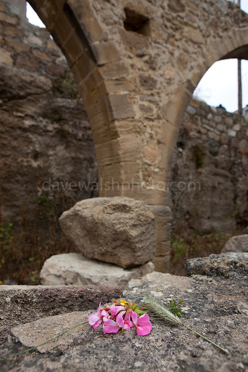 """Flowers left beside an aquaduct in the ancient Hellenic city of Polyrinia, Crete. The place name means """"many sheep"""" and it was the most fortified city in ancient Crete."""