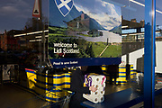 Shoppers inside a Glasgow branch of supermarket chain Lidl with corporate colours and checkout counter. On the window is a Welcome to Scotland poster that shows the Glenfinnan Monument near Fort William, where Scottish Jacobite Bonnie Prince Charlie first raised his rebel standard in 1745. Founded in the 1930s by a member of the Schwarz family, Lidl is a discount supermarket chain based in Germany that operates over 7,200 stores across Europe. The company's full name is Lidl Stiftung & Co. KG. It belongs to the holding company Schwarz Gruppe, which also owns the store chains Handelshof and hypermarket Kaufland.