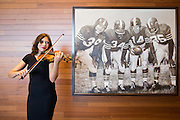 Christina Stanley of Berkeley plays the violin next to a sketch of the Million Dollar Backfield by Samantha Wendell during the Levi's Stadium Art Collection grand opening event at Levi's Stadium in Santa Clara, California, on August 1, 2014. (Stan Olszewski/SOSKIphoto for Content Magazine)