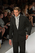 Men's black chalkstripe suit with coordinating white and black striped shirt and ascot. By Zang Toi, shown at his Spring 20132 Fashion Week show in New York.