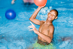 Boy throwing a ball during a game in the swimming pool at his local leisure centre,