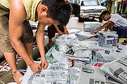 18 JUNE 2013 - YANGON, MYANMAR: Newspapers are bundled for delivery at a Yangon news agent's office. The Burmese newspaper industry has enjoyed explosive growth this year after private ownership was allowed in 2013. Private newspapers were shut down under former Burmese leader Ne Win in the early 1960s. The revitalized private press is a sign of the dramatic changes sweeping Myanmar, formerly Burma, in the last three years.      PHOTO BY JACK KURTZ