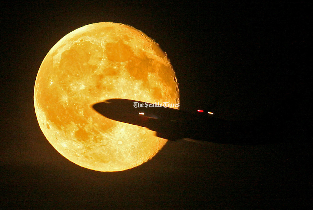 A plane out of SeaTac International Airport flies in front of the full moon Tuesday night. (Ellen M. Banner / The Seattle Times)