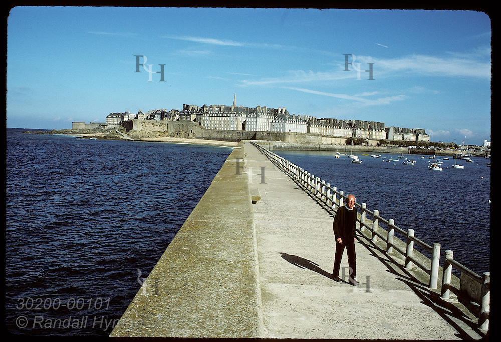 Fortress city of Saint Malo looms in distance as man walks along pier. France