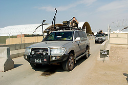 A soldier on Top Cover hides his face as a military unit leaves a secure compound within the Basrah air-station in civilian Toyota four wheel drive vehicles which have been mounted with heavy machineguns Iraq March 2005
