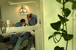 """Dr. Ala'a Al-Aswany, left, a prominent Egyptian writer and founding member of the political movement Kefaya, works on a patient in his dental office in Cairo, Egypt on April 4, 2008. """"My clinic is my window through which I can see what is happening in my society,"""" said Al-Aswany. Trained as a dentist in Cairo and Chicago, Al-Aswany has contributed numerous articles to Egyptian newspapers on literature, politics, and social issues. His second novel, The Yacoubian Building, an ironic depiction of modern Egyptian society, has been widely read in Egypt and throughout the Middle East. It was translated into English and was adapted into a film (2006) and a television series (2007) of the same name. Chicago, Al-Aswany's latest novel, is set in the American city where he had attended college."""