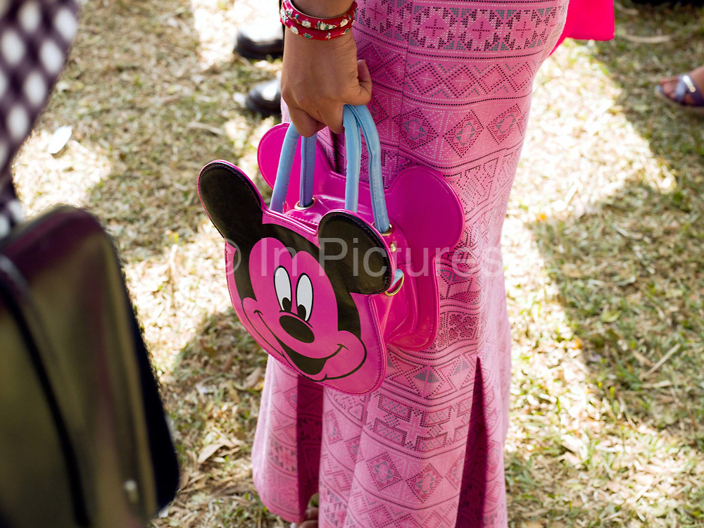 Young Hmong Der (White Hmong) woman wearing contemporary Hmong traditional costume and carrying a Mickey Mouse bag at Ban Km 52 Hmong New Year festival, Vientiane province, Lao PDR. The Hmong celebration of New Year is based on the lunar calendar. This important time is an opportunity to honour ancestors and spirits through offerings and rituals and to partake in games, sports, feasts, shows, bullfights and courtship. The Hmong are the third largest ethnic group in Laos. One of the most ethnically diverse countries in Southeast Asia, Laos has 49 officially recognised ethnic groups although there are many more self-identified and sub groups. These groups are distinguished by their own customs, beliefs and rituals.