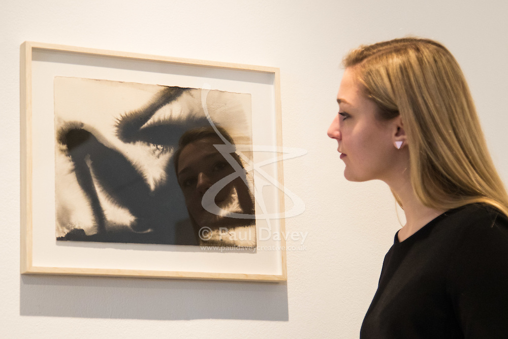 """Christies, St James, London, March 4th 2016. A woman admires Sir Anthony Gormley's  carbon and casein on paper """"Wound"""" from 2014,  at the preview for the It's Our World charity auction at Christie's. Over 40 leading artists including David Hockney, Sir Antony Gormley, David Nash, Sir Peter Blake, Yinka Shonibare, Sir Quentin Blake, Emily Young and Maggi Hambling have committed artworks to the It's Our World Auction in support of The Big Draw and Jupiter Artland Foundation, to be sold at Christie's London on 10 March 2016.<br />  ///FOR LICENCING CONTACT: paul@pauldaveycreative.co.uk TEL:+44 (0) 7966 016 296 or +44 (0) 20 8969 6875. ©2015 Paul R Davey. All rights reserved."""