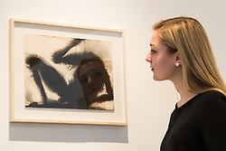 "Christies, St James, London, March 4th 2016. A woman admires Sir Anthony Gormley's  carbon and casein on paper ""Wound"" from 2014,  at the preview for the It's Our World charity auction at Christie's. Over 40 leading artists including David Hockney, Sir Antony Gormley, David Nash, Sir Peter Blake, Yinka Shonibare, Sir Quentin Blake, Emily Young and Maggi Hambling have committed artworks to the It's Our World Auction in support of The Big Draw and Jupiter Artland Foundation, to be sold at Christie's London on 10 March 2016.<br />  ///FOR LICENCING CONTACT: paul@pauldaveycreative.co.uk TEL:+44 (0) 7966 016 296 or +44 (0) 20 8969 6875. ©2015 Paul R Davey. All rights reserved."