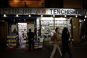 Twee meisjes lopen voorbij een boekwinkel in het centrum van Osaka