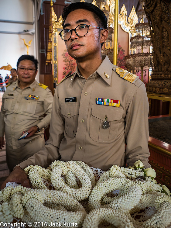 """19 DECEMBER 2016 - BANGKOK, THAILAND:  An employee of the Royal Household hold flower garlands during the """"Spirit Appeasing"""" Ceremony for the Royal Chariots at the Bangkok National Museum. The chariots will be used to take the body of Bhumibol Adulyadej, the Late King of Thailand, and members of the Royal funeral cortege to the cremation site on Sanam Luang for His Majesty's cremation. This will be the first cremation of a Thai King since 1950, when King Bumibol's brother, Rama VIII, Ananda Mahidol, was cremated. The design of the royal crematorium is based on Buddhist cosmology, with the main peak of Mount Sumeru (also known as Meru in Hindu cosmology) at center and eight other peaks signifying the levels of the universe. The crematorium will be decorated with mythical creatures such as garuda, angels, and Himmapan Forest creatures. The structure and funeral pyre will stand just over 50 meters tall. The exact date of the King's cremation has not been set yet but is expected to be late next year.    PHOTO BY JACK KURTZ"""