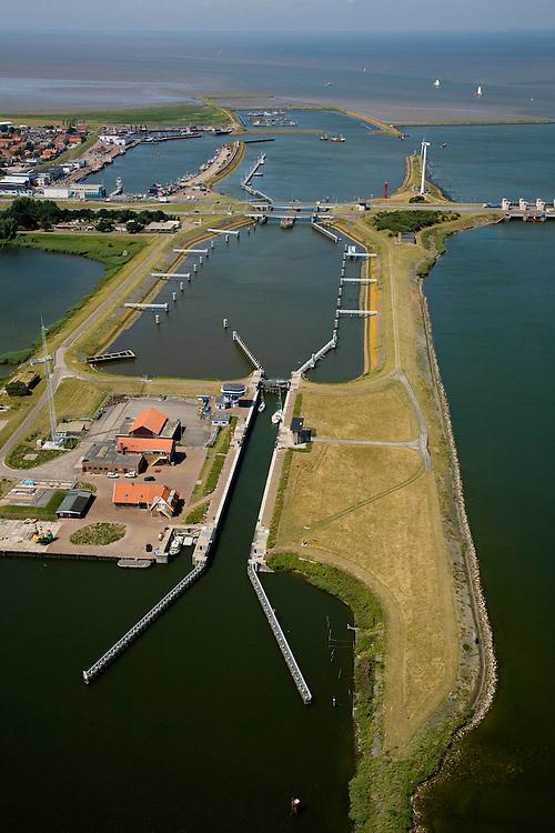 Nederland, Noord-Holland, Den Oever, 14-07-2008; Afsluitdijk, waterkering tussen Waddenzee en IJsselmeer (rechts en onder, voorheen Zuiderzee). Aanleg van de dijk vormde onderdeel Zuiderzeewerken, initiatief van ingenieur Cornelis Lely. In de dijk de Stevinsluizen, spuisluizen of uitwaterende sluizen. Het 'eiland' (rechts) heet Robbenplaat.<br /> The IJsselmeer Dam or Enclosure Dam, dike between the provinces Noord-Holland and Friesland, left Wadden sea, below and right former Zuyder Zee (now inner sea/lake). In the foreground locks for shipping and sluicing surplus water. luchtfoto (toeslag), aerial photo (additional fee required)<br /> foto/photo Siebe Swart