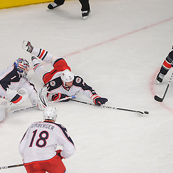 New York Rangers defenseman Michael Del Zotto (4) sends a pass across the crease past Columbus Blue Jackets goalie Steve Mason (1) and defenseman Fedor Tyutin (51), which turned into an assist on the Rangers' game-winning goal during overtime NHL action between the Columbus Blue Jackets and the New York Rangers at Madison Square Garden in New York, N.Y. The Rangers defeated the Blue Jackets 3-2 in overtime.