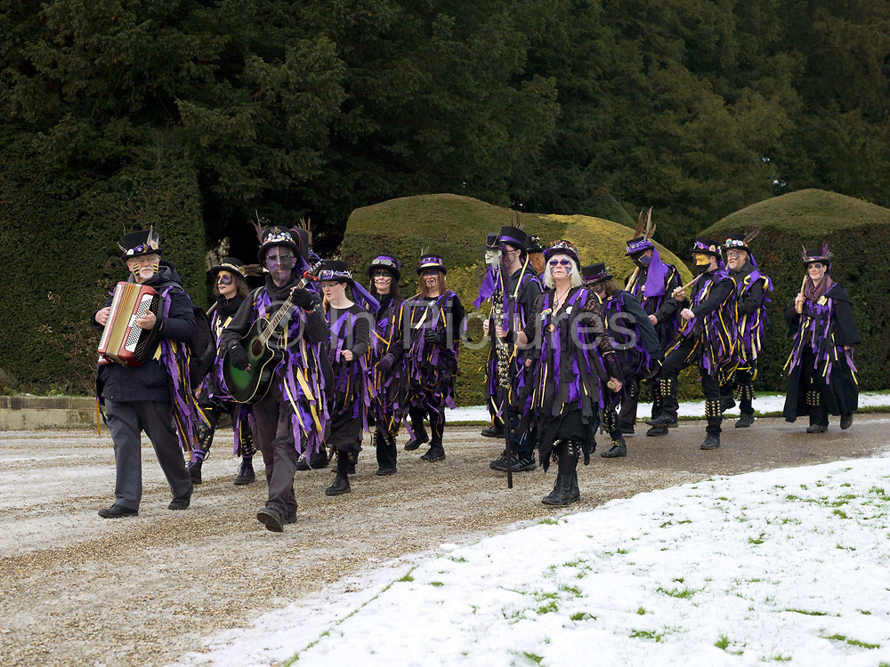 Rack-a-back Morris Men dancing a stick dance at an orchard-visiting wassail at Sledmere House, Yorkshire Wolds, UK on 20th January 2018. Wassail is a traditional Pagan winter celebration in cider-producing regions of England, reciting incantations and singing to the trees to promote a good harvest for the coming year. Pieces of toast soaked in cider are hung in the branches to attract robins to the tree as these are said to be the good spirits of the orchard. To ward off evil spirits, villagers scare them away by banging pots and pans and making as much noise as possible