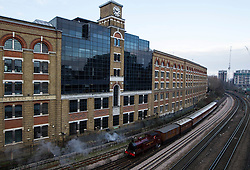 © Licensed to London News Pictures. 13/01/2013, London, UK. The newly restored Met Locomotive No. 1 steam engine leaves a train depot in London, Sunday, Jan. 13, 2013. The engine will travel through part of the original underground route to mark the 150th anniversary of the opening of the world's first underground in January 1863, and linked to it will be the oldest surviving operational underground carriage, the Metropolitan Railway Jubilee Carriage 353, a set of four Chesham carriages and the world's oldest electric locomotives in service, No 12 Sarah Siddons. Photo credit : Sang Tan/LNP