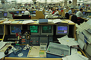 A detail of a bankers desk photogrpahed in 1993, with computer screens and a large keyboard and calculator plus a packet of Rothmans cigarettes and lighter, on 22nd June 1993, in London, England.