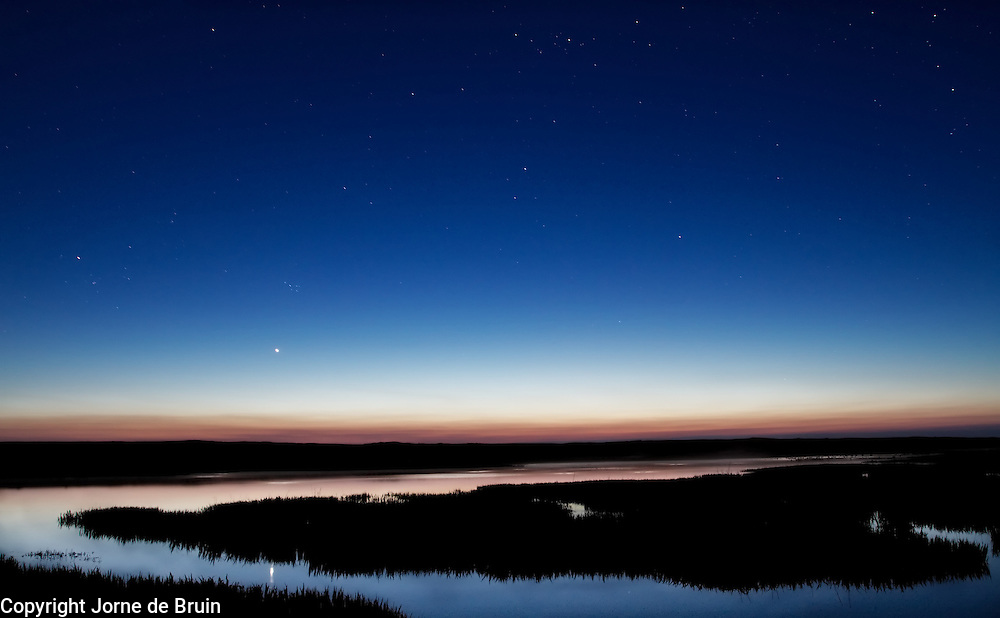 A dune lake just after sunset under a starry sky on the island of Texel in the Netherlands