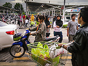 08 JULY 2013 - PATTANI, PATTANI, THAILAND:  People leave and walk into the Big C grocery store in Pattani, Thailand, Monday afternoon, the day before Ramadan. Ramadan starts July 9 and Monday was the last day observant Muslims were able to eat and drink during daylight hours. Muslims fast during the holy month of Ramadan, taking breakfast before dawn and not eating again until after sunset. The restaurants in Pattani, a Muslim majority city in southern Thailand, were packed Monday afternoon and evening.   PHOTO BY JACK KURTZ