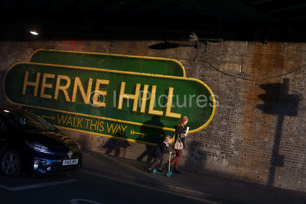 A mother and child pedestrians walk beneath the large sign under the railway bridge announcing Herne Hill, Lambeth SE24 on 18th November 2016, on 18th November 2016, in south London, England.