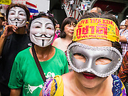 """02 JUNE 2013 - BANGKOK, THAILAND:  An anti-government protester wearing a We Love the King headband, marches with other anti-government protesters. The so called White Mask protesters are strong supporters of the Thai monarchy. About 300 people wearing the Guy Fawkes mask popularized by the movie """"V for Vendetta"""" and Anonymous, the hackers' group, marched through central Bangkok Sunday demanding the resignation of Prime Minister Yingluck Shinawatra. They claim that Yingluck is acting as a puppet for her brother, former Prime Minister Thaksin Shinawatra, who was deposed by a military coup in 2006 and now lives in exile in Dubai.    PHOTO BY JACK KURTZ"""