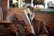 A walk along the River Thames on the Southbank in London. A man reads the Guardian newspaper in the BFI cafe. This area is very popular especially on the weekends for Londoners to walk and see different arts, culture and entertainment.