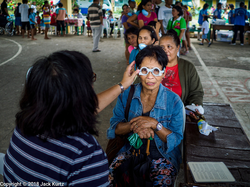 """22 JANUARY 2018 - GUINOBATAN, ALBAY, PHILIPPINES: A woman in an evacuation center in Guinobatan gets her eyes checked during a clinic at the shelter. Several communities in Guinobatan were hit ash falls from the eruptions of the Mayon volcano and many people wore face masks to protect themselves from the ash. There were a series of eruptions on the Mayon volcano near Legazpi Monday. The eruptions started Sunday night and continued through the day. At about midday the volcano sent a plume of ash and smoke towering over Camalig, the largest municipality near the volcano. The Philippine Institute of Volcanology and Seismology (PHIVOLCS) extended the six kilometer danger zone to eight kilometers and raised the alert level from three to four. This is the first time the alert level has been at four since 2009. A level four alert means a """"Hazardous Eruption is Imminent"""" and there is """"intense unrest"""" in the volcano. The Mayon volcano is the most active volcano in the Philippines. Sunday and Monday's eruptions caused ash falls in several communities but there were no known injuries.    PHOTO BY JACK KURTZ"""
