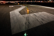 """A wide night view looking down on the rubber-stained of runway 27R at Heathrow Airport. During a time-exposure and partially-lit by the headlights and spotlights of an airfield emergency vehicle, we see the giant numbers 27 that landing pilots will see from a mile away as they descend towards the airport's threshold. The numbers relate to the compass bearing that the line of the runway takes: In this case 270 degrees from north and has a parallel southern twin. Across the number two we also see a set of taxiway lights that help the steering pilot navigate across the airfield and line-up on the departing runway. .From writer Alain de Botton's book project """"A Week at the Airport: A Heathrow Diary"""" (2009). ."""