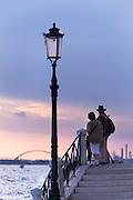 Couple at sunrise, Fondamenta Zattere allo Spirito Santo. Venice, Italy, Europe