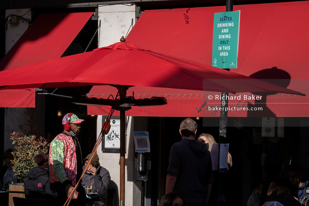 On the day that the UK government eased Covid restrictions to allow non-essential businesses such as shops, pubs, bars, gyms and hairdressers to re-open, a social distancing sign and red awning covering a busy bar serving meals and drinks outdoors in Soho, on 12th April 2021, in London, England.